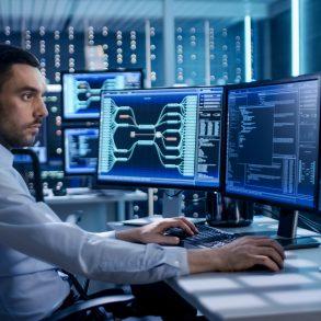 Especialista em segurança cibernética trabalhando em frente de 3 telas de computador, rastreando ataques cibernéticos