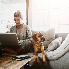 mulher sentada no sofa com um laptop no colo e um cachorro ao lado