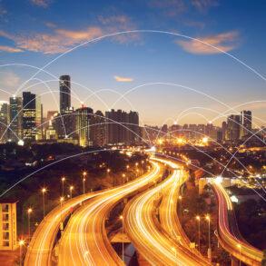 vista aérea de uma cidade, com diversas luzes e carros passando. Remete a conectividade