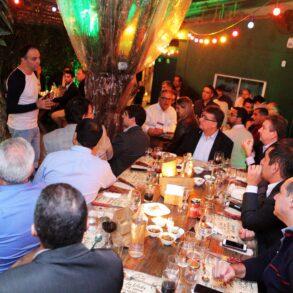 Pessoas reunidas em um jantar, assistindo a uma palestra ministrada pela ODATA em evento de relacionamento